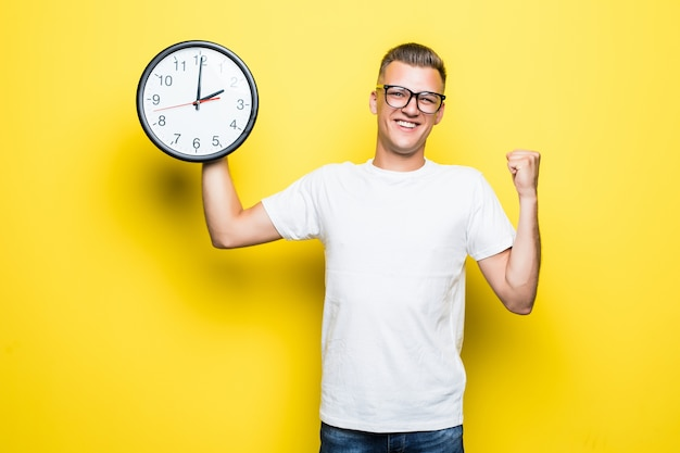 Handsome man in white t-shirt and transperent glasses hold big clock in one hand Free Photo