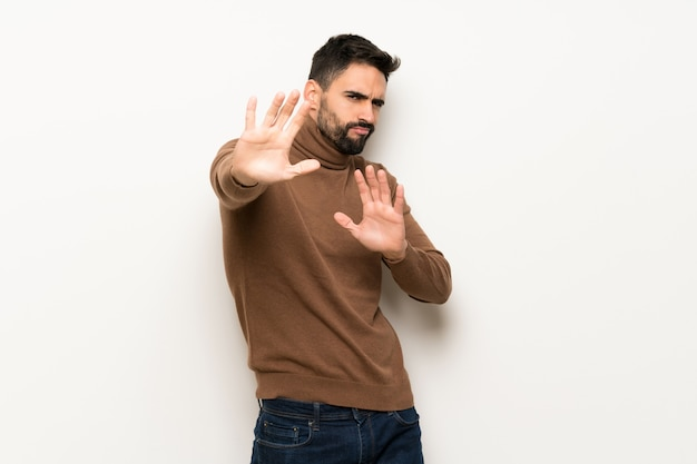 Handsome man over white wall is a little bit nervous and scared stretching hands to the front Premium Photo