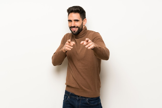 Handsome man over white wall points finger at you while smiling Premium Photo