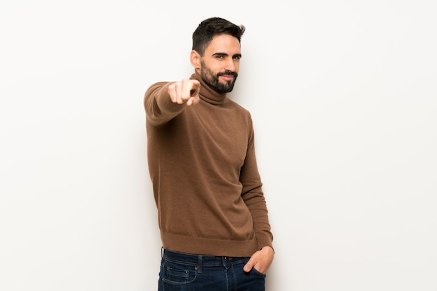 Handsome man over white wall points finger at you with a confident expression Premium Photo
