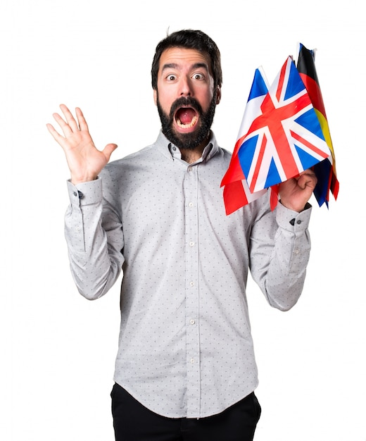 Handsome man with beard holding many flags and making surprise gesture Free Photo