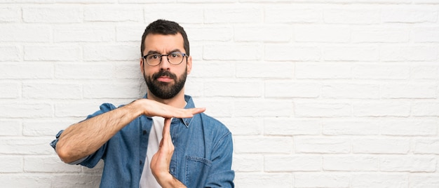 Handsome man with beard over white brick wall making time out gesture Premium Photo