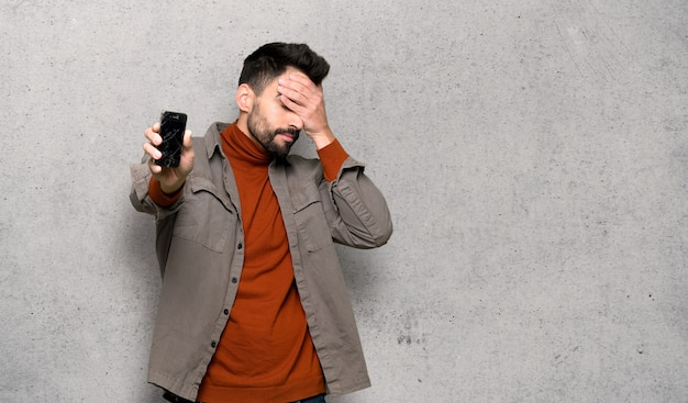 Handsome man with beard with troubled holding broken smartphone over textured wall Premium Photo