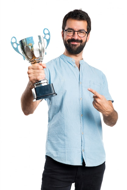 Handsome man with blue glasses holding a trophy Free Photo