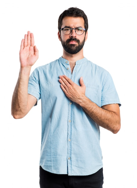 Handsome man with blue glasses making an oath Free Photo
