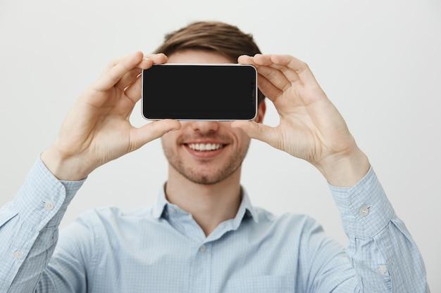 Bell'uomo con setola, sorridente che mostra il display dello smartphone Foto Gratuite