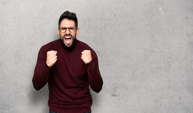 Handsome man with glasses frustrated by a bad situation over textured wall Premium Photo