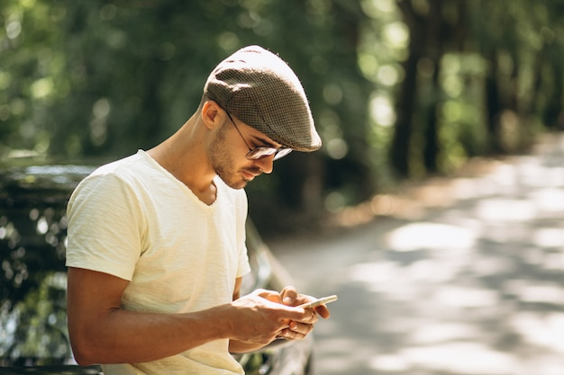 Handsome man with phone by car Free Photo