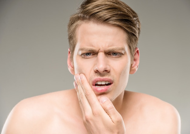 Handsome man with pure skin touching his face. Premium Photo