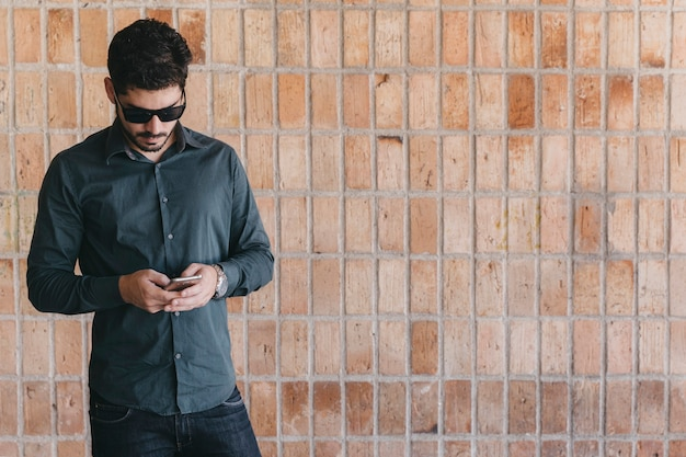 Handsome man with smartphone near brick wall Free Photo