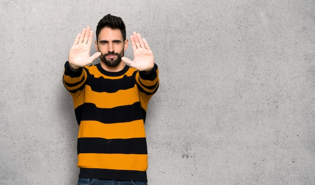 Handsome man with striped sweater making stop gesture for disappointed Premium Photo