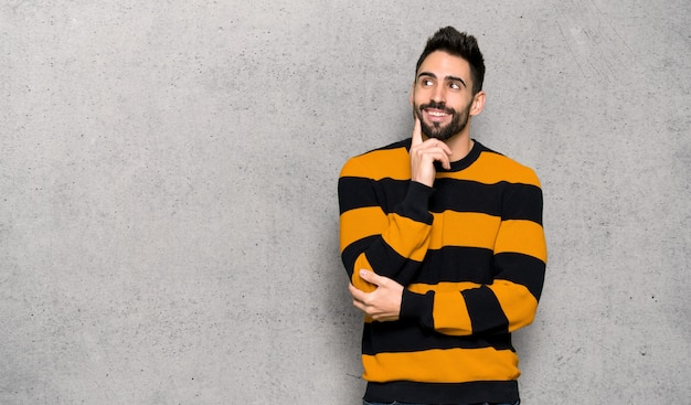 Handsome man with striped sweater thinking an idea while looking up over textured wall Premium Photo