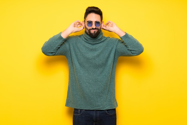 Handsome man with sunglasses covering ears with hands. frustrated expression Premium Photo