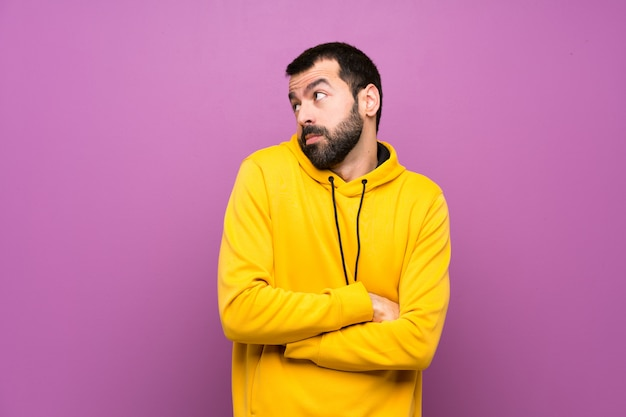 Handsome man with yellow sweatshirt making doubts gesture while lifting the shoulders Premium Photo