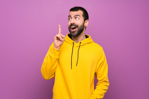 Handsome man with yellow sweatshirt thinking an idea pointing the finger up Premium Photo