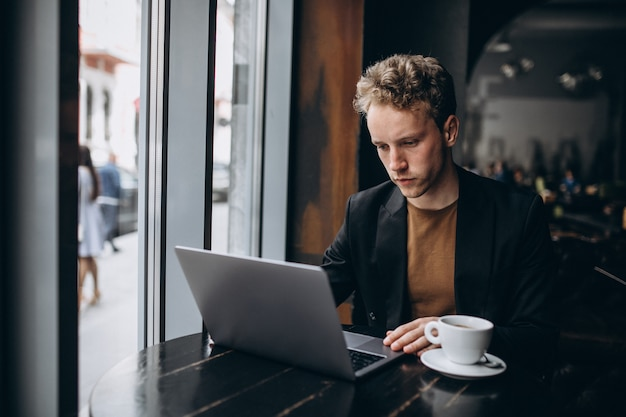 Handsome man working on a computer in a cafe and drinking coffee Free Photo