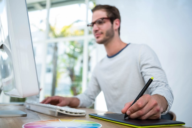 Handsome man working on computer and taking notes in a bright office Premium Photo