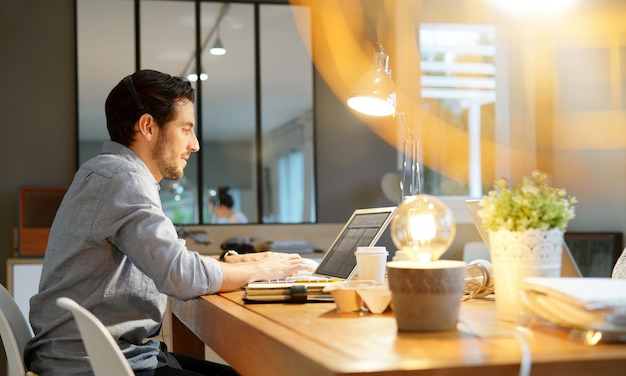 Handsome man working on laptop in co working space Premium Photo