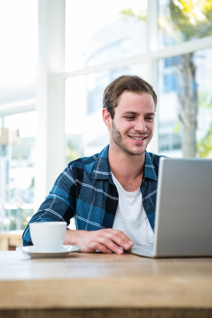 Handsome man working on laptop with cup of coffee in a bright office Premium Photo