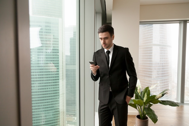 Handsome manager searching contact in smartphone Free Photo