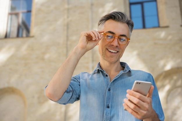 Handsome mature businessman holding smartphone, communication, reading news. Premium Photo