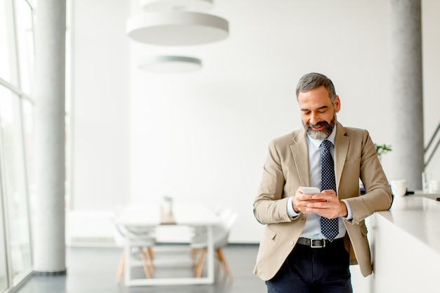 Handsome mature businessman  with mobile phone in the office Premium Photo