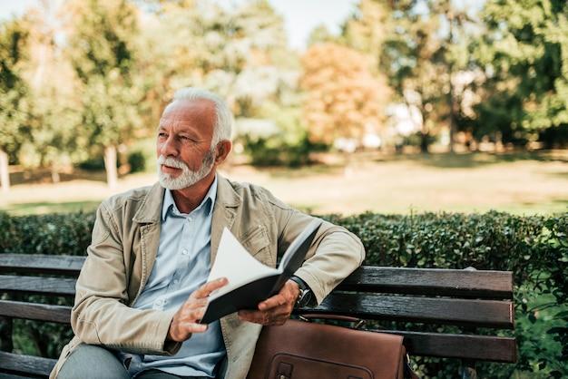 Handsome mature man reading book outdoors. Premium Photo