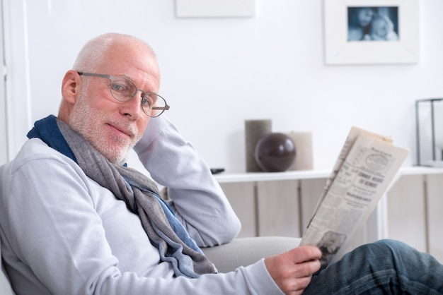 Handsome mature man reading newpaper on sofa Premium Photo