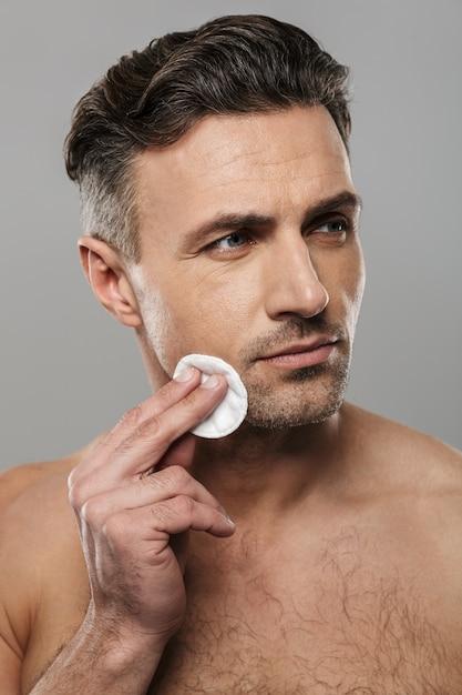 ハンサムな成熟した男は彼の肌の世話をします。 Premium写真