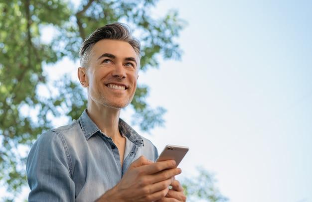 Handsome mature man using mobile phone, shopping online Premium Photo