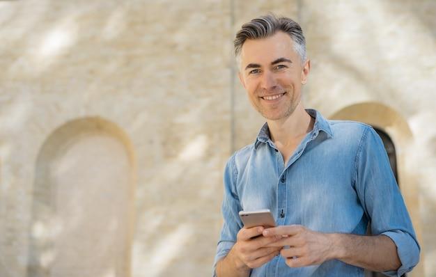 Handsome mature man using mobile phone Premium Photo