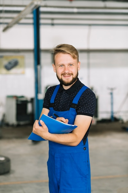 Handsome mechanic with pen and folder Free Photo