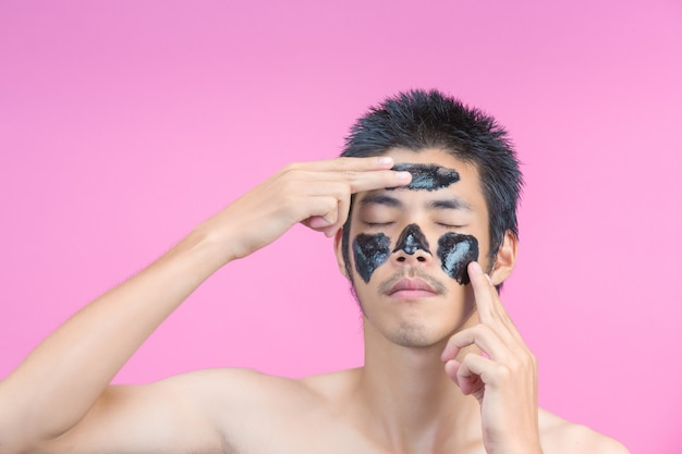 Handsome men are using their hands to apply black cream on their faces and have a pink . Free Photo