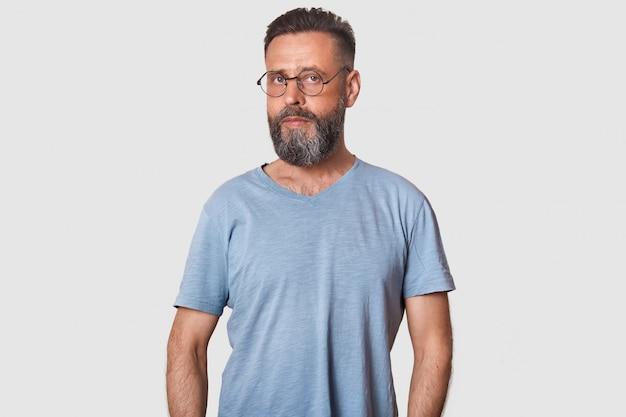 ハンサムな中年の男、深刻な表情、カジュアルな服装と丸みを帯びた光学ガラス、白で隔離されるポーズ。 無料写真