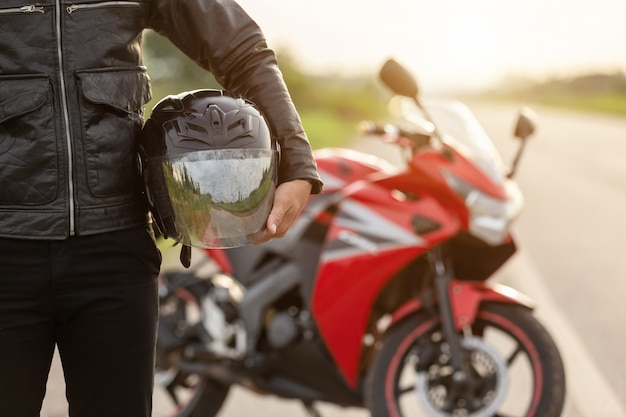 Handsome motorcyclist wear leather jacket, holding helmet on the road Premium Photo