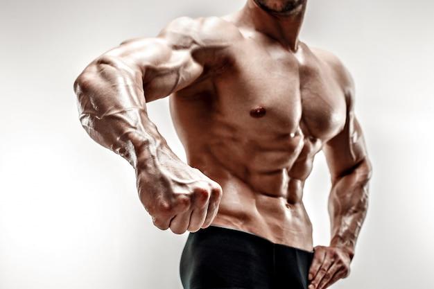 Handsome muscular bodybuilder demonstrates his fist and vein, blood vessels. studio shot on white background. Premium Photo
