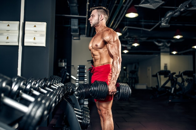 Handsome muscular man posing at a gym Premium Photo
