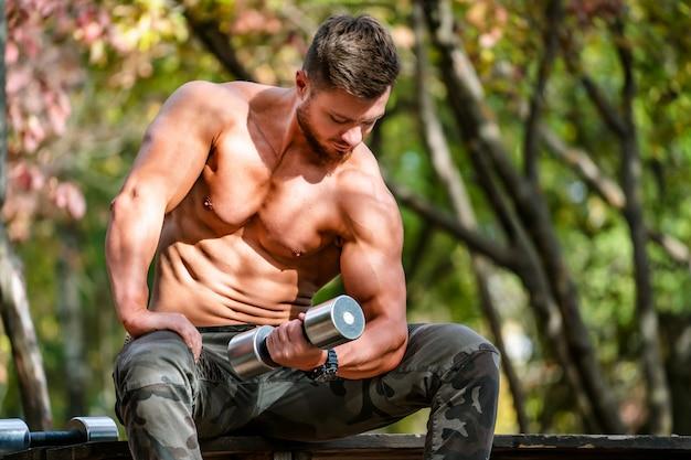 잘 생긴 근육 질의 벗은 덩어리 야외 야외 설정에서 남자. 건강한 몸을 보여줍니다. 반쯤 벗은 운동가. 공원 경치. Dumbbel, 흐린 배경 작업. 프리미엄 사진