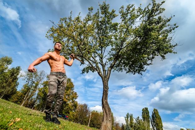잘 생긴 근육 질의 벗은 덩어리 야외 야외 설정에서 남자. 건강한 몸을 보여줍니다. 반쯤 벗은 운동가. 공원 경치. 프리미엄 사진