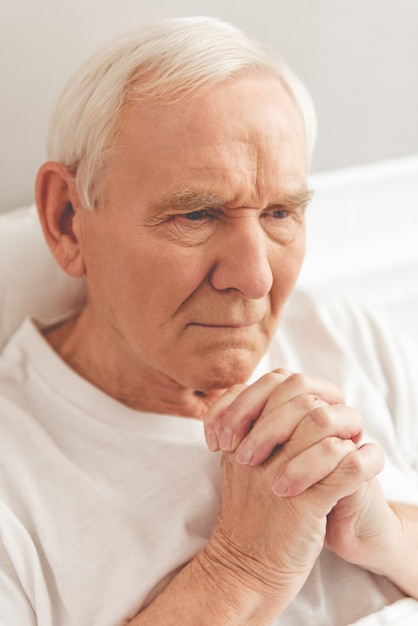 Handsome old man is praying while lying in bed in hospital. Premium Photo