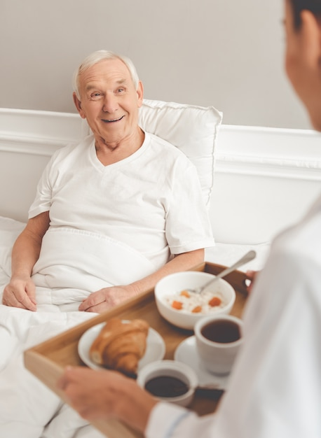 Handsome old patient is getting his meal from nurse. Premium Photo