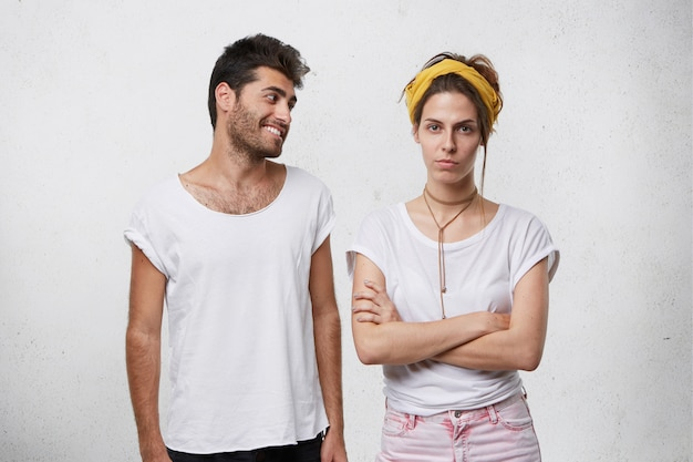 Handsome positive bearded male in white t-shirt trying to convince or apologize to his angry upset girlfriend in yellow headband who is looking offended, keeping her arms crossed Free Photo