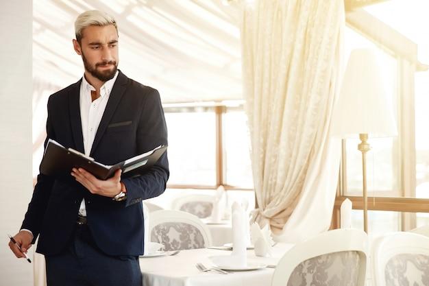 Il direttore di ristorante bello sta controllando il processo di lavoro Foto Gratuite