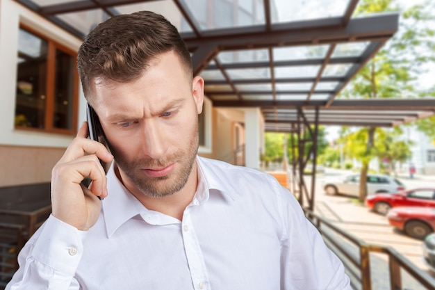 Handsome salesman talking on mobile phone Premium Photo