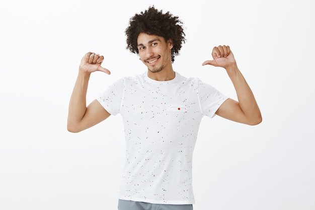 Handsome sassy dark-skinned man pointing at himself, bragging or show-off Free Photo