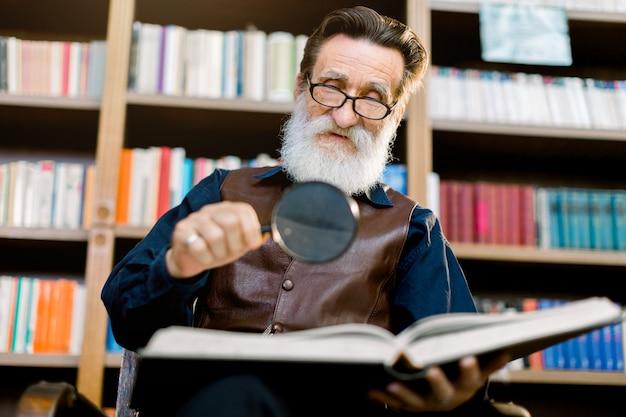 ハンサムなシニアのひげを生やした男性、司書または図書館の教授、本棚の背景の上に座って、虫眼鏡を押しながら本を読んで Premium写真