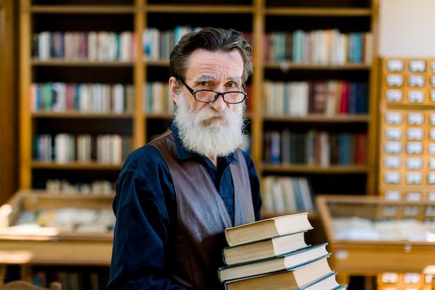 ハンサムなシニアひげを生やした引退した男、司書または教師、図書館で本を選択する、本のスタックを保持している、カメラを見て、背景に本の棚 Premium写真