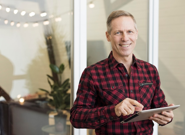 Handsome senior man holding a tablet Free Photo