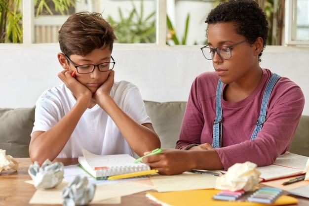 ハンサムな真面目なアジアの少年は、家庭教師と一緒に語学研修を受け、机に一緒に座り、宿題とレッスンの練習をし、メモ帳に焦点を合わせ、大学の入学試験やセミナーの準備をします 無料写真