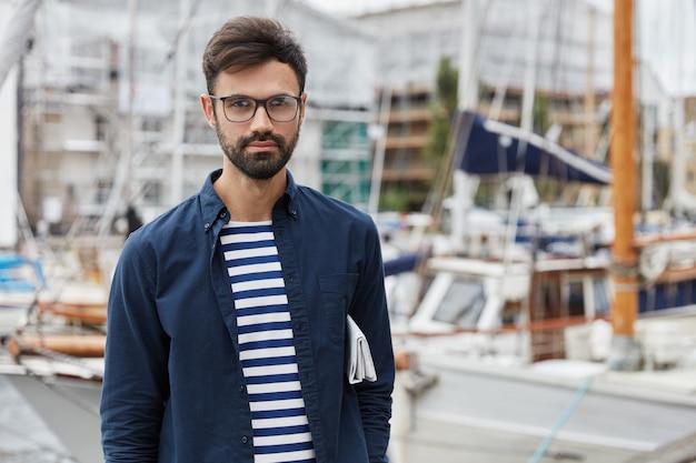Красивый серьезный бородатый молодой парень идет по гавани Бесплатные Фотографии